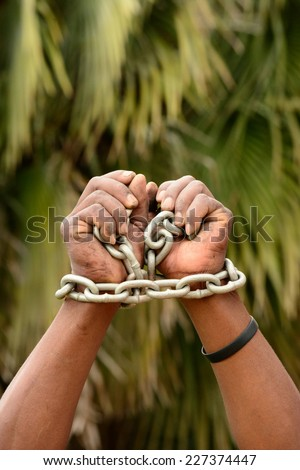 Two black hands of a young South African Xhosa man with big chain around the wrists in front of blurry green palm tree background. - stock photo