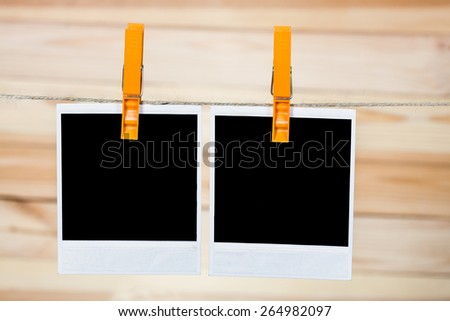 Two black instant photo, hanging on the clothesline on wooden background. - stock photo