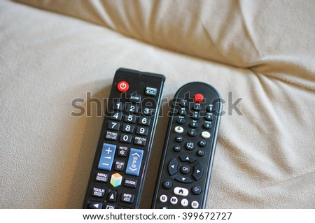 Two black plastic tv remotes on sofa - stock photo
