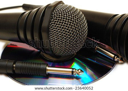 Two black wired karaoke microphones with gray metal grill on isolated background and CD (DVD) disk. - stock photo