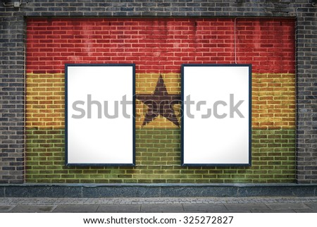 Two blank billboards attached to a buildings exterior brick wall which has a Ghana flag painted on it. - stock photo