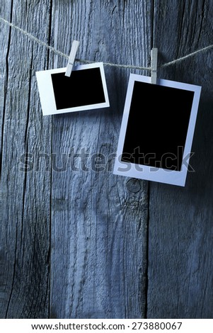 Two blank photographs hanging on a clothesline, blue tone. - stock photo