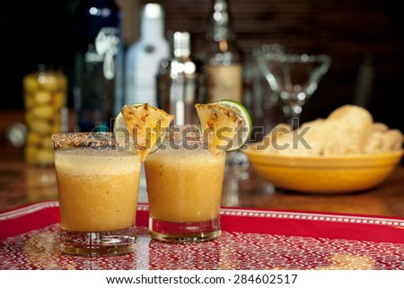 Two blended pineapple margaritas sit ready to serve with chips and a bar in the background. - stock photo