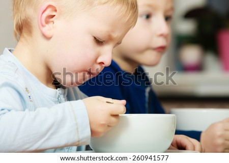 Two blond brothers boys kids children eating corn flakes breakfast morning meal at the table. Home. - stock photo