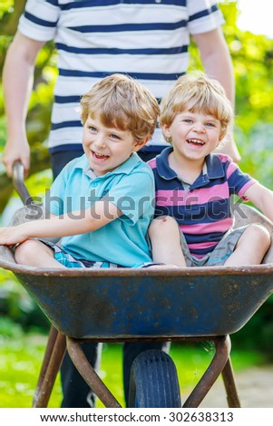 Two blond little boys having fun in a wheelbarrow pushing by father in domestic garden, on warm sunny day. Active outdoors games for kids in summer. - stock photo