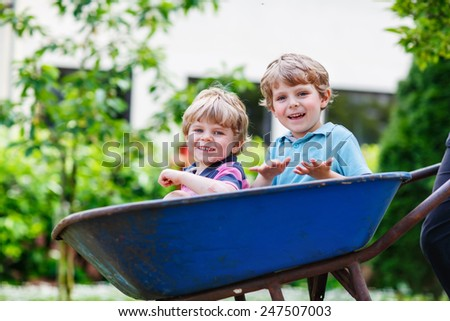 Two blond little sibling boys having fun in a wheelbarrow pushing by dad in domestic garden, on warm sunny day. Active outdoors games for kids in summer. - stock photo