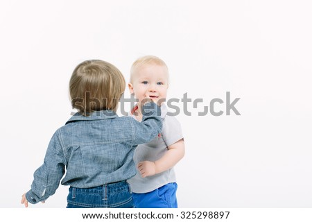 two blonde baby boy interacting with each other over white background - stock photo