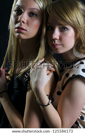 Two blonde Caucasian young women in a back embrace, looking at camera, portrait - stock photo