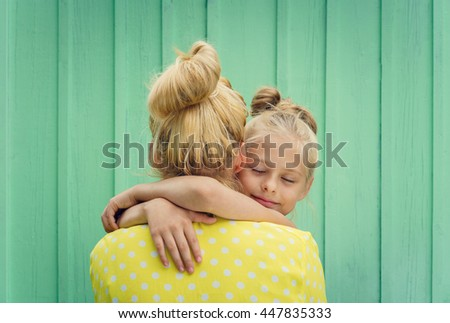 Two blondes Mom and daughter smiling, hugging - stock photo