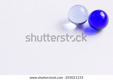 Two blue and clear glass marbles - Upper right - stock photo