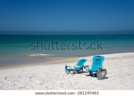 Two Blue Beach Chairs and a Tote Bag on the Beach  - stock photo