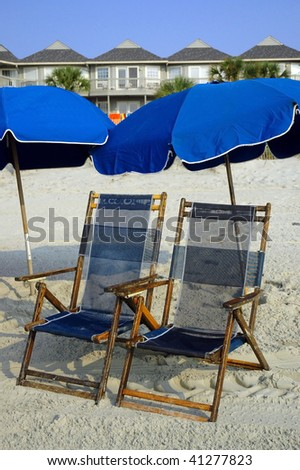 two blue beach chairs under blue umbrellas - stock photo