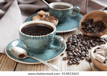Two blue cups of black coffee, sugar cubes in a wooden bowls and scattered coffee beans on a background of a linen cloth - stock photo