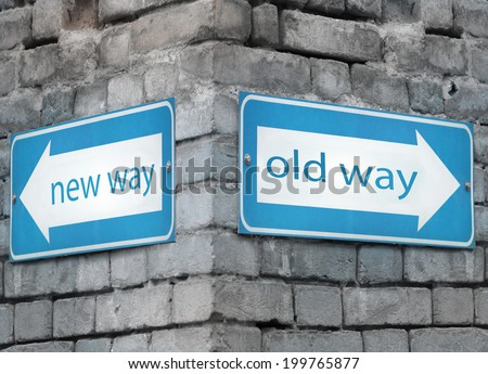 Two blue light directions arrow at the angle on a grey old brick wall with the text new and old way - stock photo