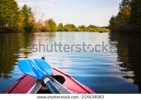 Two blue paddles are lying on kayak. Kayaking on a river. - stock photo