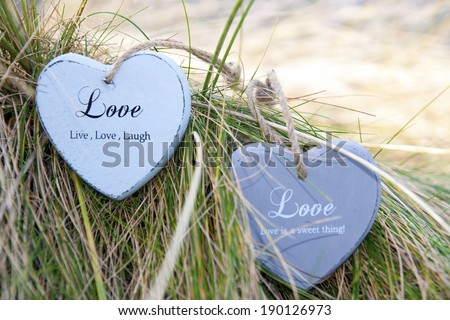 two blue wooden love heart in dunes on an Irish beach - stock photo