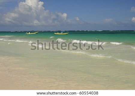 Two boats and white sand beach with blue water - stock photo