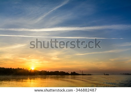 Two boats docking early in the morning near the pier. Horizontal view of a couple of boats loading up cargo in a summer morning over a sunrise sky on background. - stock photo