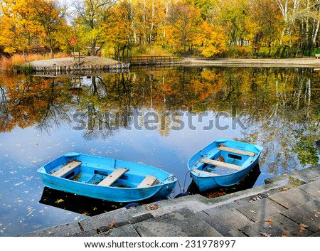 Two boats on the lake, pond. Autumn, water, landscape. Yellow leaves of the trees. - stock photo