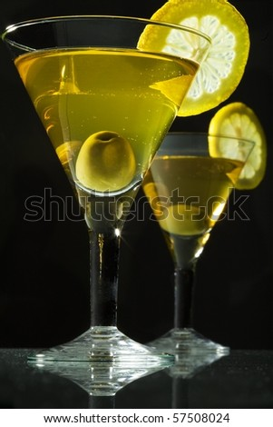 Two bocals  of martini with olive and lemon on black background - stock photo