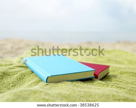 Two books lying on a towel at the beach. - stock photo
