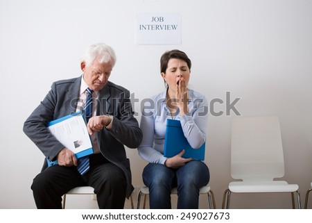 Two bored candidates waiting for job interview - stock photo