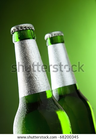 two bottles of beer on a green background - stock photo