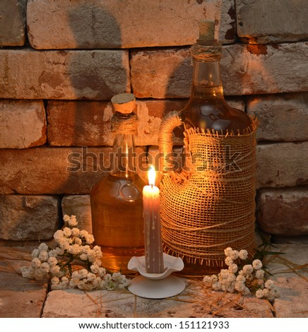 Two bottles of cider with burning candle in country cellar on stone background - stock photo