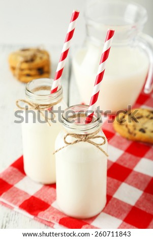 Two bottles of milk with striped straws and cookies on white wooden background - stock photo