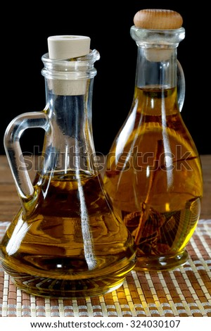 Two bottles of olive oil on rustic table - stock photo