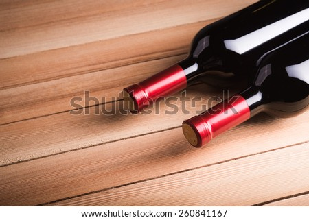 Two bottles of wine on wood background - stock photo