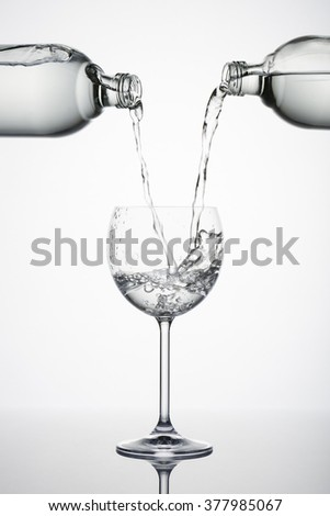 two bottles pouring water in glass with splashes on white background - stock photo