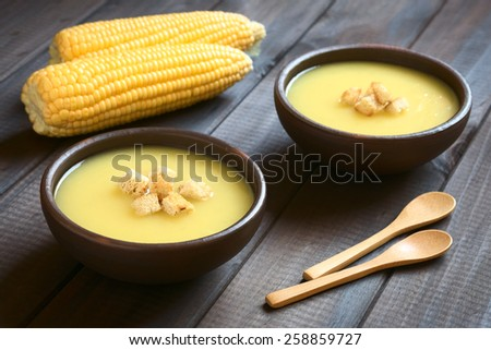 Two bowls of cream of corn soup with croutons on top, photographed on dark wood with natural light (Selective Focus, Focus on the front of the croutons on the first soup) - stock photo