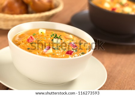Two bowls of fresh homemade sweet potato and apple soup with thyme (Selective Focus, Focus in the middle of the soup) - stock photo