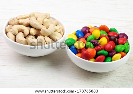 Two bowls with cashew nuts and colorful round sweets - stock photo