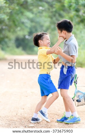 Two boy angry and fighting by punch on the other on the urban road during summer time.. - stock photo