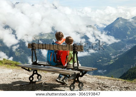 Two boy sit on bench in Alps - stock photo