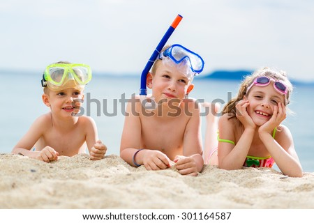 Two boys and a girl enjoy their time on the beach and scuba diving - stock photo