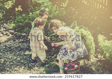 Two boys and a girl search for colorful Easter eggs during an egg hunt outdoors in a garden in the spring. Part of a series.   Filtered for a retro, vintage look. - stock photo