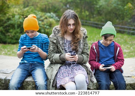two boys and a teenage girl sitting outside with phones - stock photo