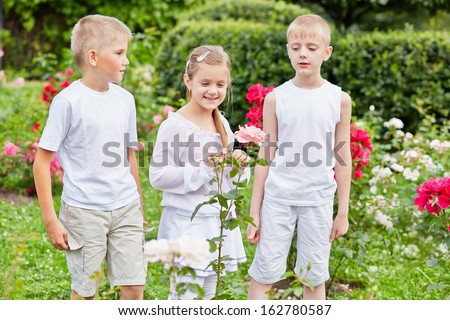 Two boys and one girl stand on lawn planted with roses in summer park - stock photo