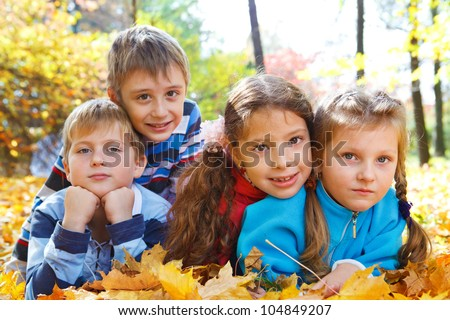 Two boys and two girls in autumn park - stock photo