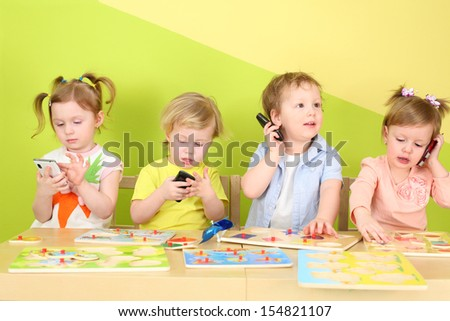 Two boys and two girls with phones in their hands are sitting at a table with toys - stock photo