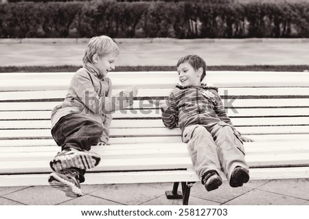 two boys are playing rock-paper-scissor on the bench - stock photo