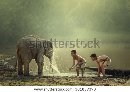 Two boys are playing splashing water with baby elephant at pond - stock photo