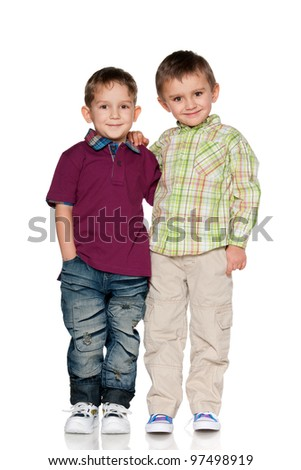 Two boys are standing together; isolated on the white background - stock photo