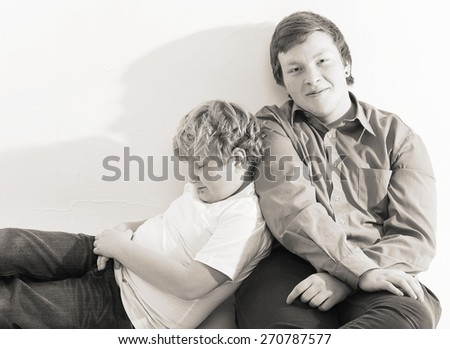 two boys brothers friends  studio portrait on white background playing black and white - stock photo