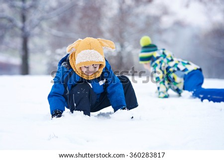 Two boys, brothers, playing in the snow with snowballs, wintertime - stock photo