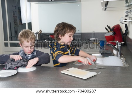 Two boys doing the dishes in a modern kitchen. - stock photo