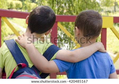 Two boys, friends, or brothers, holding around the shoulders, back view.  - stock photo